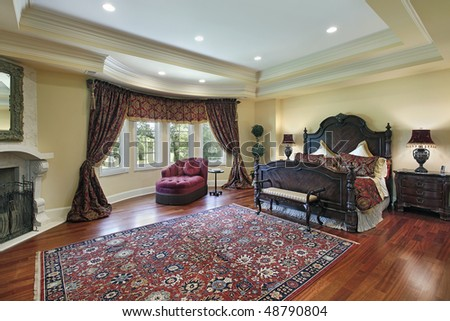 Luxury master bedroom with recessed ceiling and fireplace - stock photo