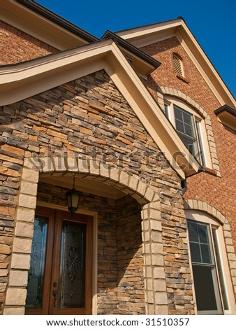 Luxury Model Home Exterior with stone arch entrance