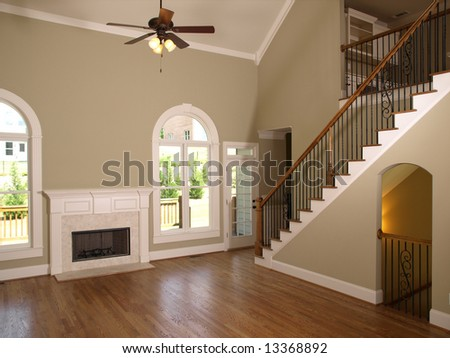 Luxury Model Home Living Room with fireplace and staircase - stock photo