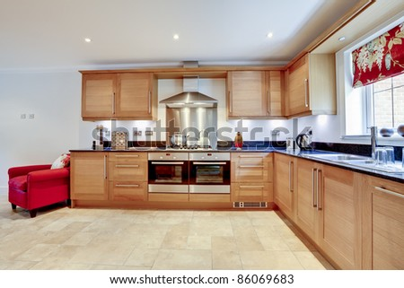 Luxury modern fitted kitchen with built in appliances and granite worktop - stock photo