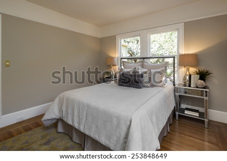 Luxury modern home bedroom with rug, view window and cherry wooden flooring. - stock photo