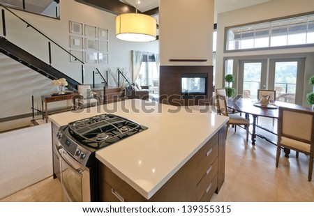 Luxury modern kitchen with the living room and the fireplace at the back. Interior design. - stock photo