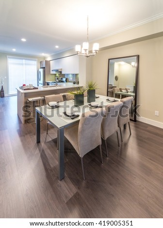 Luxury modern living suite. Nicely decorated dining table and the kitchen at the back.  Interior design. - stock photo