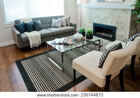 Luxury modern living suite, room with sofa and chairs and nicely decorated with vase coffee table. Interior design of a brand new house. - stock photo