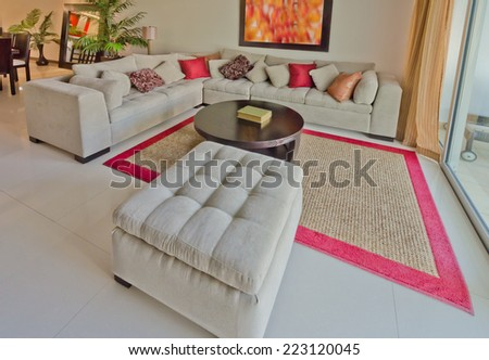 Luxury modern living suite,  room with sofa and pillows and nicely decorated coffee table. Interior design of a brand new house. - stock photo