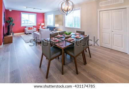 Luxury modern living suite with nicely decorated dining table and the living room behind. Interior design. - stock photo