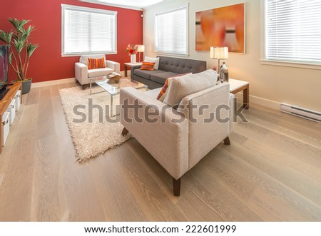 Luxury modern living suite with red color walls, room with sofa and chairs and nicely decorated with vase coffee table. Interior design of a brand new house. - stock photo