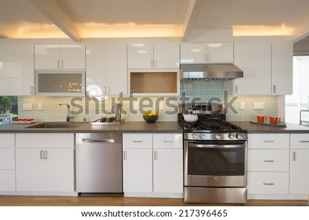 Luxury modern styled kitchen with white cabinets, stainless steel appliances, grey granite counter and back light.  - stock photo
