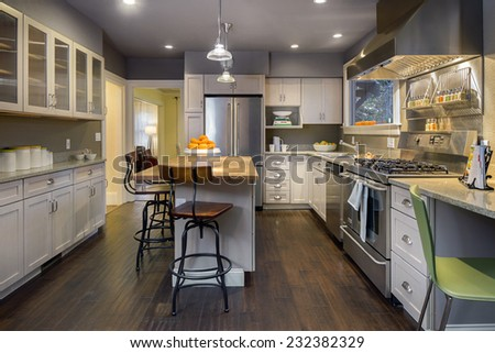 Luxury modern styled kitchen with white wooden cabinets, stainless steel appliances, granite counter and kitchen island with wooden counter. - stock photo