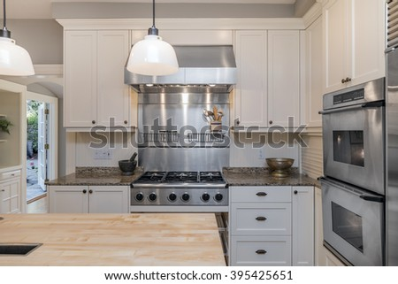 Luxury modern styled kitchen with white wooden cabinets, stainless steel appliances, new elegant wooden kitchen island and marble counters. - stock photo