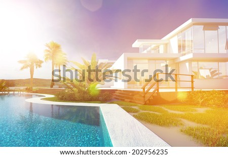 Luxury modern white house with angular walls and large windows overlooking a tropical landscaped garden with palm trees and curving blue swimming pool - stock photo