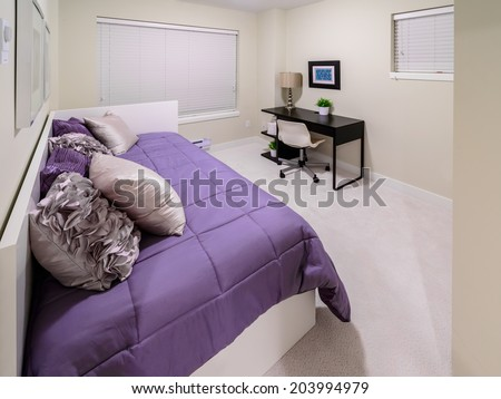 Luxury nicely decorated modern bedroom with some elements of den, home office with the table and the office chair at the back. Interior design of a brand new house. - stock photo