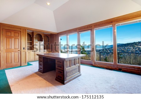Luxury office room with rich wood furniture, carpet floor, cathedral ceiling and amazing floor-to-ceiling window with impressive view on mountain landscape - stock photo