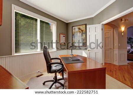 Luxury office room with wooden desk, leather whirlpool chair. Grey walls with white plank trim - stock photo
