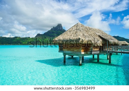 Luxury overwater thatched roof bungalow in a honeymoon vacation resort in the clear blue lagoon with a view on the tropical island of Bora Bora, near Tahiti, in French Polynesia.