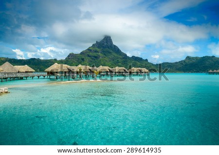 Luxury overwater thatched roof bungalow resort in a vacation resort in the clear blue lagoon with a view on the tropical island of Bora Bora, near Tahiti, in French Polynesia. - stock photo