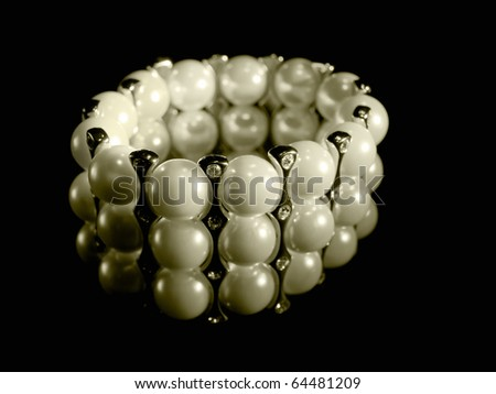 Luxury pearl bracelet on black background - stock photo