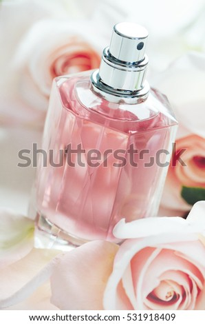 Luxury perfume bottle with pink roses petals. Fashion makeup and body care products.