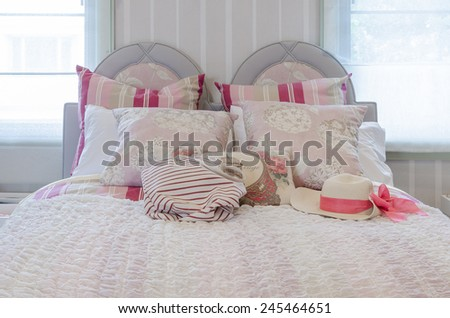 luxury pink color scheme bedroom with bag and hat on bed at home - stock photo