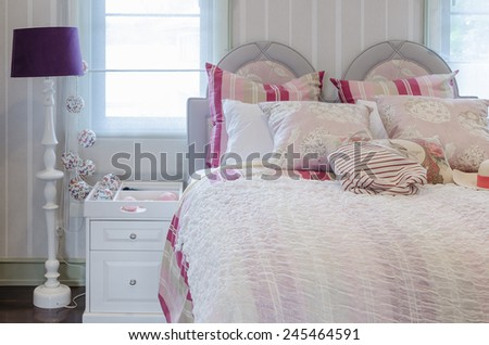 luxury pink color scheme bedroom with white table and lamp at home - stock photo