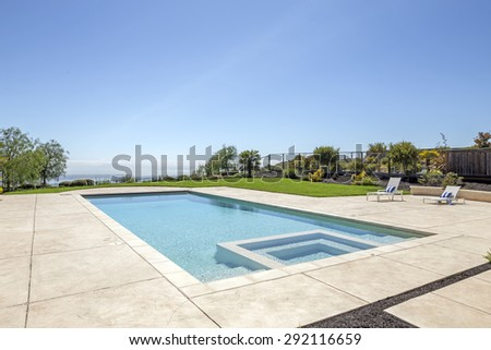 Luxury Pool with Jacuzzi / Whirlpool framed in sandstone with deckchairs. - stock photo