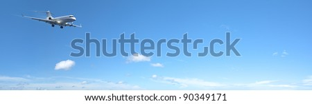 Luxury private jet is maneuvering for landing in a clear blue sky. Panoramic composition in high resolution. - stock photo