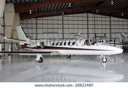 Luxury private jet parked in a hangar - stock photo