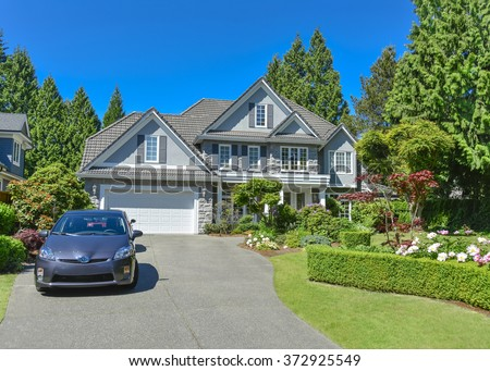 Luxury residential house with green hedge and landscaping in front. Family house surrounded by trees with blue sky background. Suburban house with double garage and car parked on concrete driveway. - stock photo