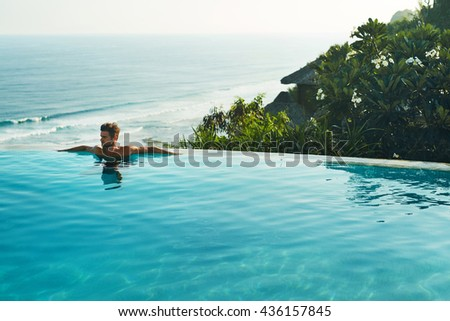 Luxury Resort. Man Relaxing In Infinity Swimming Pool Water. Beautiful Happy Healthy Male Model Enjoying Summer Travel Vacation At Tropical Spa Hotel In Indonesia, Sea View. Summertime Relax Concept - stock photo