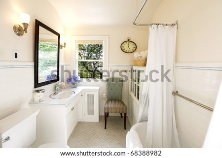 Luxury Romantic bathroom with iron tub and cream color and purple flowers. - stock photo