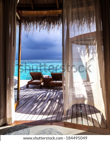 Luxury romantic place for honeymoon, beautiful wooden bungalow on the water, two deckchair on the terrace, vacation on the islands, summer time concept  - stock photo