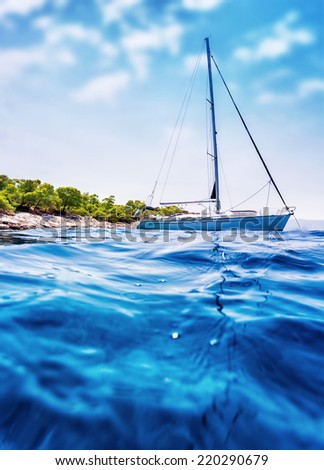 Luxury sailboat floating in the sea near tropical island, romantic cruise along Greece, summer holidays and vacations concept  - stock photo