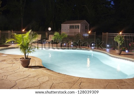 Luxury salt water pool and patio at night. - stock photo