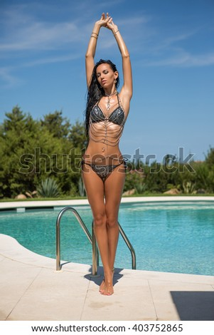 luxury sexy young woman in bikini with many accessories, chains, and jewelry is posing in the swimming pool - stock photo