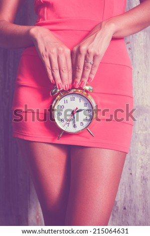 luxury slim pretty woman holding alarm clock in front of her - stock photo