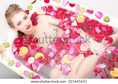 luxury smiling spa: elegant blue eyes young pinup lady with silk skin having fun relaxing in water bath & looking at camera on colorful copy space background, portrait