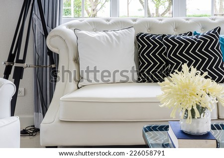 luxury sofa in living room with yellow flower in vase at home - stock photo