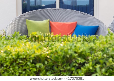 Luxury sofa  wicker and color pillows in the garden, front blur tree. - stock photo