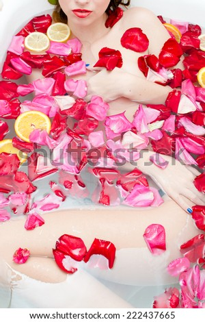 luxury spa queen: beautiful sexy elegant young lady with red lipstick & silk skin having fun lying in water bath relaxing on colorful rose petals copy space background