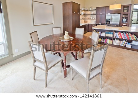 Luxury spacious  modern dining room with the table and chairs an the kitchen at the back. Interior design.