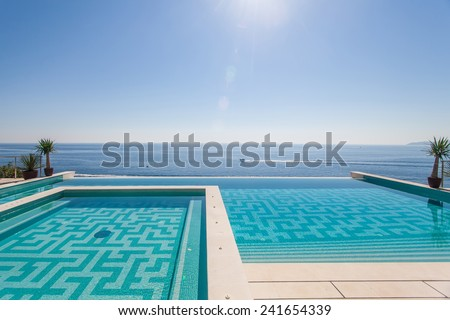Luxury swimming pool and blue water at the resort with beautiful sea view. All inclusive vacations, summer vacation, travel, travel agency, vacation, vacation packages, vacation rentals - stock photo