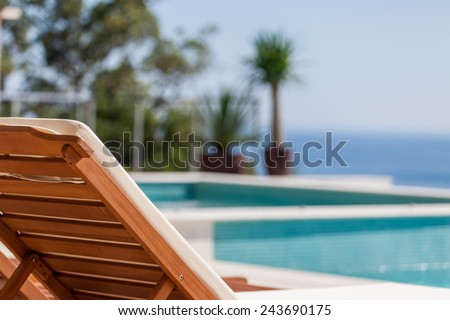 Luxury swimming pool and deck chair at the resort with beautiful sea view - stock photo