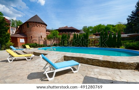 Luxury swimming pool beside the hotel in medieval british castle style. Landscape design of resort territory. Swimming pool outdoors. Blue water in summer park.