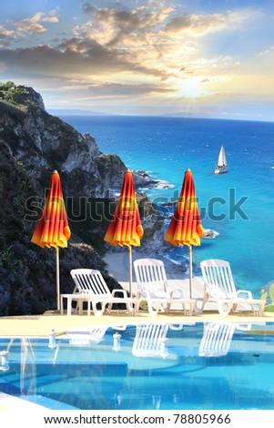 Luxury swimming pool with azure sea - stock photo
