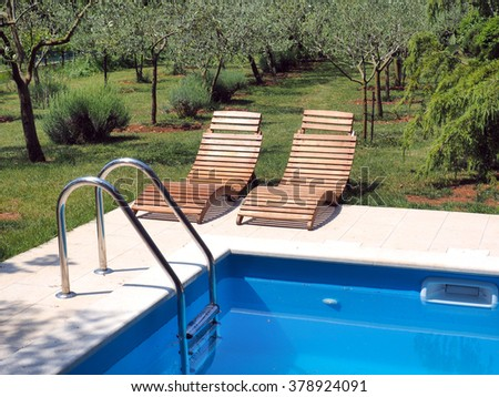 Luxury swimming pool with green grass and chairs - stock photo