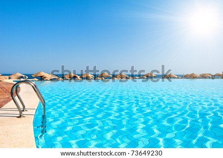 Luxury swimming pool with sunny sky - stock photo