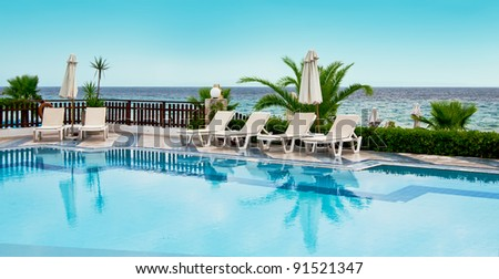 Luxury swimming pool with white fashion deckchairs - stock photo