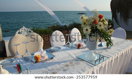 Luxury Table Setting with Candlestick by the Sea. Outdoor Wedding Reception Setting. Wedding reception place ready for guests. - stock photo