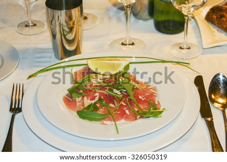 Luxury table setting with plate of meat carpaccio and lime - stock photo