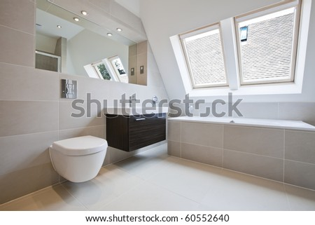Luxury tiled modern bathroom with wall mounted 'floating' style wc and hand-basin - stock photo